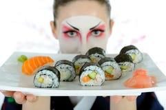 Mujer hermosa del geisha de Japón con el sushi Imagen de archivo