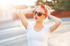 Mujer hermosa del inconformista con los labios rojos y las gafas de sol que se colocan adentro Imagenes de archivo