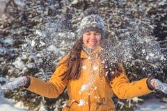 Mujer hermosa del invierno que juega con nieve Foto de archivo libre de regalías