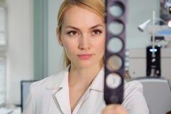 Mujer hermosa del oculista con el dispositivo oftalmológico en el gabinete imagenes de archivo