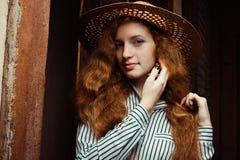 Mujer hermosa del pelirrojo con el pelo rizado largo en la presentación del sombrero de paja Imágenes de archivo libres de regalías