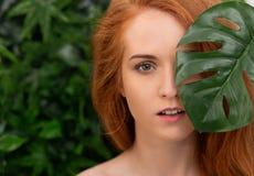 Mujer hermosa del pelirrojo con la piel perfecta en hojas tropicales imagenes de archivo
