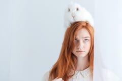 Mujer hermosa del pelirrojo que presenta con el conejo en su cabeza Foto de archivo libre de regalías
