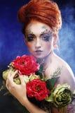 Mujer hermosa del redhair que sostiene las flores fotografía de archivo