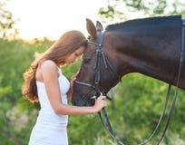 Mujer hermosa del retrato con el caballo siguiente del pelo largo Fotos de archivo libres de regalías