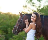 Mujer hermosa del retrato con el caballo siguiente del pelo largo Foto de archivo libre de regalías
