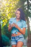 Mujer hermosa del retrato que manda un SMS con su teléfono Fotos de archivo libres de regalías