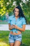 Mujer hermosa del retrato que manda un SMS con su teléfono Imagen de archivo libre de regalías