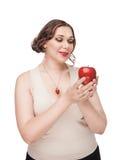 Mujer hermosa del tamaño extra grande con la manzana Foto de archivo