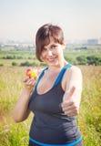 Mujer hermosa del tamaño extra grande de la aptitud con la manzana que muestra los pulgares para arriba Fotos de archivo libres de regalías