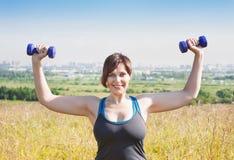 Mujer hermosa del tamaño extra grande que ejercita con pesas de gimnasia imagen de archivo libre de regalías