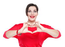 Mujer hermosa del tamaño extra grande que hace forma del corazón con sus manos Focu Fotografía de archivo