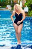 Mujer hermosa del tamaño extra grande que presenta en la piscina imagen de archivo libre de regalías