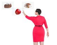 Mujer hermosa del tamaño extra grande que toma la decisión entre sano y el unhe Imagenes de archivo