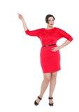 Mujer hermosa del tamaño extra grande en el vestido rojo que muestra en algo Foto de archivo libre de regalías