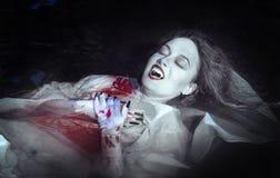 Mujer hermosa del vampiro que miente en el río Imágenes de archivo libres de regalías