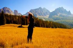 Mujer hermosa delante de las montañas asombrosas que sienten la libertad Fotografía de archivo