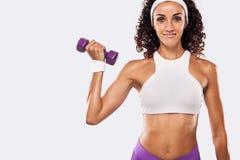 Mujer hermosa deportiva con pesa de gimnasia que ejercita en el fondo blanco para permanecer apto Imagen de archivo