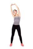 Mujer hermosa deportiva joven que estira los brazos y detrás Foto de archivo libre de regalías