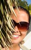 Mujer hermosa detrás de la palma Imagen de archivo