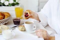 Mujer hermosa detrás de una tabla blanca que come un cruasán con pero Fotografía de archivo libre de regalías