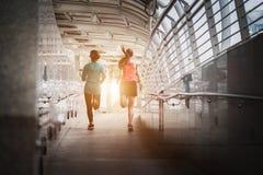 Mujer hermosa dos que corre sobre el puente durante puesta del sol fotos de archivo