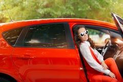 Mujer hermosa elegante en coche rojo imagenes de archivo
