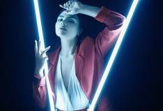 Mujer hermosa elegante en un traje de moda rojo que presenta con las luces de neón imagenes de archivo