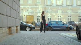 Mujer hermosa elegante en vestido negro que camina en la calle Ella que mira alrededor almacen de metraje de vídeo