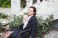 Mujer hermosa elegante joven en las gafas de sol que se sientan en un café de consumición al aire libre del café foto de archivo