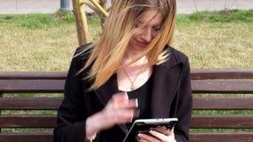 Mujer hermosa elegante que manda un SMS en la tableta adentro metrajes