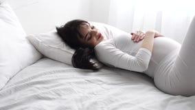 Mujer hermosa embarazada que miente en cama y el vientre de caricia del bebé almacen de video