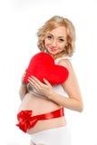 Mujer hermosa embarazada que sostiene la almohada roja del corazón en sus manos aisladas en el fondo blanco Fotos de archivo libres de regalías