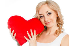Mujer hermosa embarazada que sostiene la almohada roja del corazón en sus manos aisladas en el fondo blanco Imagen de archivo