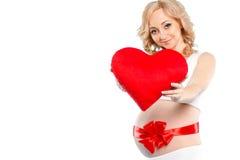 Mujer hermosa embarazada que sostiene la almohada roja del corazón en sus manos aisladas en el fondo blanco Fotos de archivo
