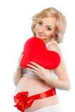 Mujer hermosa embarazada que sostiene la almohada roja del corazón en sus manos aisladas en el fondo blanco Foto de archivo libre de regalías