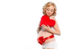 Mujer hermosa embarazada que sostiene la almohada roja del corazón en sus manos aisladas en el fondo blanco Imagen de archivo libre de regalías
