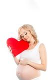 Mujer hermosa embarazada que sostiene la almohada roja del corazón en sus manos aisladas en el fondo blanco Fotografía de archivo libre de regalías