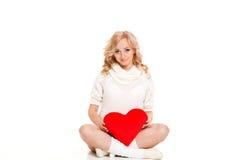 Mujer hermosa embarazada que sostiene la almohada roja del corazón en sus manos aisladas en el fondo blanco Imágenes de archivo libres de regalías