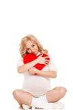 Mujer hermosa embarazada que sostiene la almohada roja del corazón en sus manos aisladas en el fondo blanco Foto de archivo