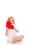Mujer hermosa embarazada que sostiene la almohada roja del corazón en sus manos aisladas en el fondo blanco Fotografía de archivo