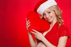 Mujer hermosa embarazada que sostiene la almohada roja del corazón en sus manos aisladas en fondo rojo Imagenes de archivo