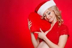 Mujer hermosa embarazada que sostiene la almohada roja del corazón en sus manos aisladas en fondo rojo Fotografía de archivo libre de regalías