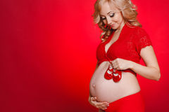 Mujer hermosa embarazada que sostiene la almohada roja del corazón en sus manos aisladas en fondo rojo Imágenes de archivo libres de regalías