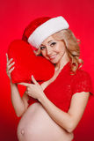 Mujer hermosa embarazada que sostiene la almohada roja del corazón en sus manos aisladas en fondo rojo Foto de archivo
