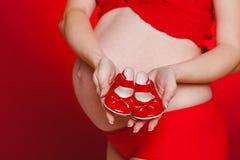 Mujer hermosa embarazada que sostiene la almohada roja del corazón en sus manos aisladas en fondo rojo Imagen de archivo