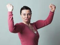Mujer hermosa emocionada 40s que dobla sus músculos para arriba Fotos de archivo libres de regalías