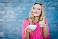 Mujer hermosa emocionante que bebe de la taza que muestra los pulgares para arriba Imagen de archivo libre de regalías
