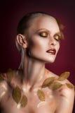 Mujer hermosa en accesorios con las hojas del oro Foto de archivo