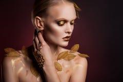 Mujer hermosa en accesorios con las hojas del oro Foto de archivo libre de regalías